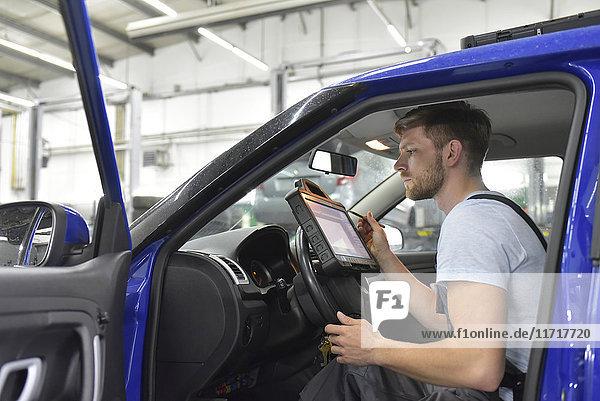 Kfz-Mechaniker in einer Werkstatt mit Diagnosecomputer im Auto