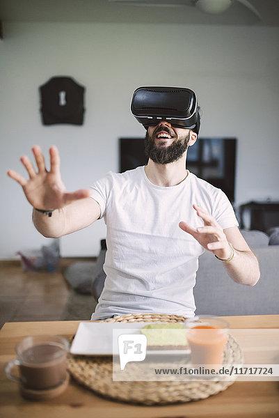 Mann beim Frühstück mit Virtual-Reality-Brille