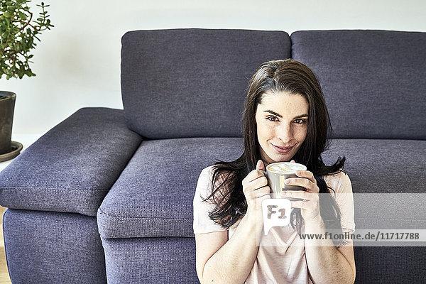 Lächelnde junge Frau mit Kaffeetasse zu Hause