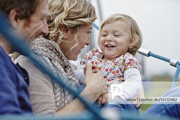Glückliche Familie auf dem Spielplatz im Kletternetz