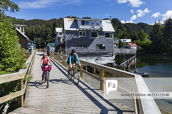 Mother and daughter ride bicycles on the historic oceanside boardwalk in Seldovia  Southcentral Alaska  USA
