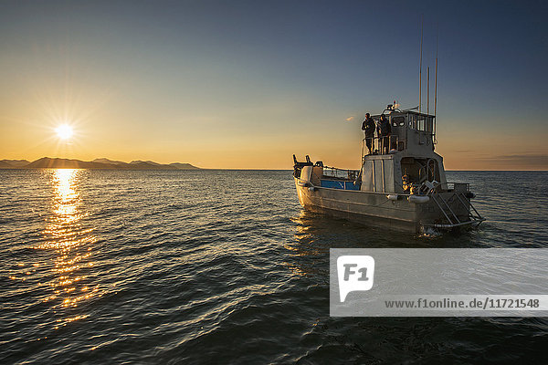 The sun rises in the Bristol Bay region as a commercial fishing boat floats in calm waters  Southwest Alaska  USA
