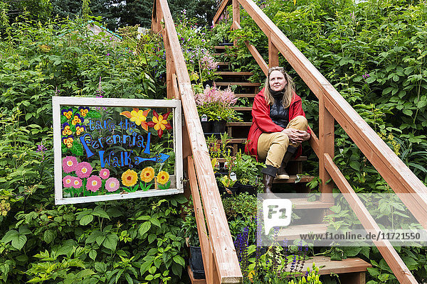 Woman sitting on stairs in a lush garden  Seldovia  Southcentral Alaska  USA