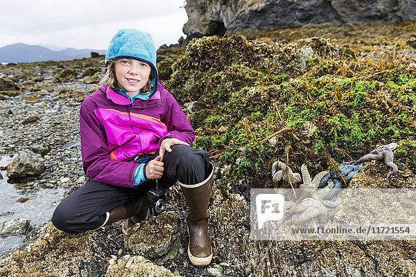 Young girl crouches in a tidal pool next to several stranded starfish  Hesketh Island  Southcentral Alaska  USA