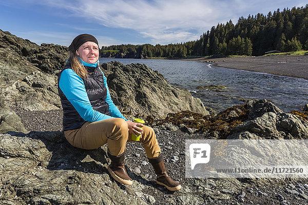 Woman sitting along a rocky shore near Seldovia  Southcentral Alaska  USA