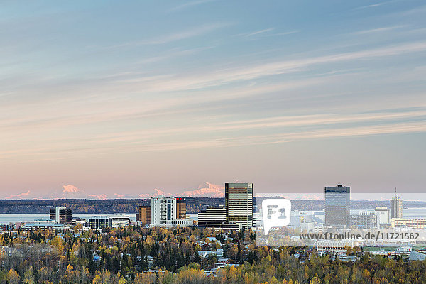 Aerial perspective of warm sunset light on Denali and Mt. Foraker beyond the buildings of downtown Anchorage  Southcentral Alaska  USA  Fall