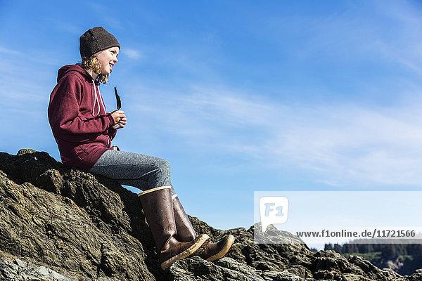 Young girl sits on a rocky shoreline  Seldovia  Southcentral Alaska  USA