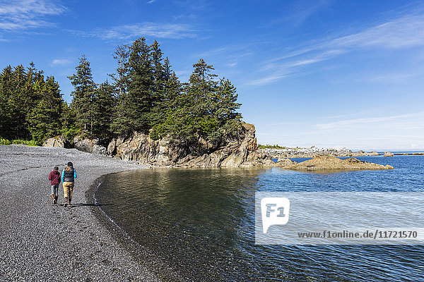 Mother and daughter walking on the beach near Seldovia  Southcentral Alaska  USA