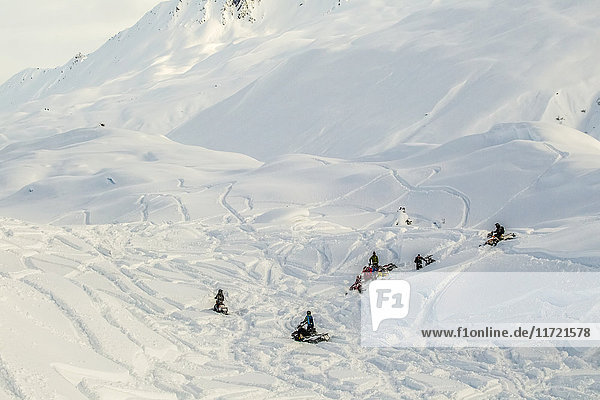 A group of snowmobilers converge while riding up at Thompson Pass  Southcentral Alaska  USA