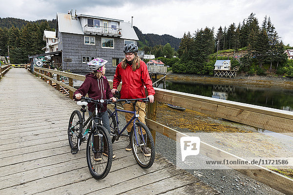 Mother and daughter with bicycles on the historic Seldovia oceanside boardwalk,  Southcentral Alaska,  USA