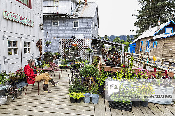 Woman sits in a chair along the historic Seldovia boardwalk  Southcentral Alaska  USA