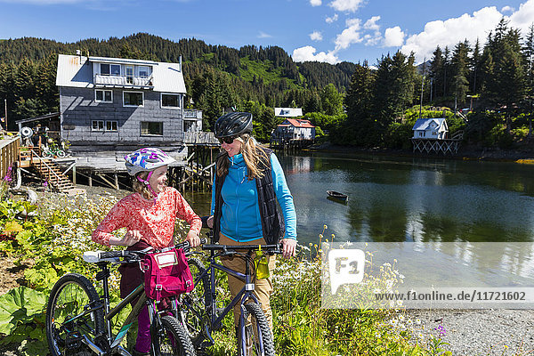 Mother and daughter with bicycles next to the Seldovia Slough on a sunny day  Southcentral Alaska  USA