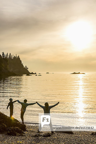 Mother and two kids silhouetted as they play along Hesketh Island  Southcentral Alaska  USA