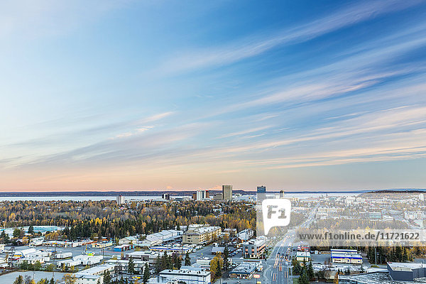 Warm sunset light on Denali and Mt. Foraker beyond the buildings of downtown Anchorage  Southcentral Alaska  USA  Fall