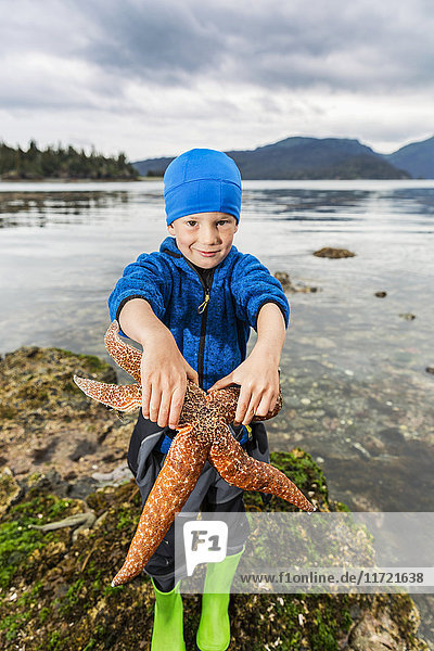 Young boy showing off a large sea star  Hesketh Island  Southcentral Alaska  USA