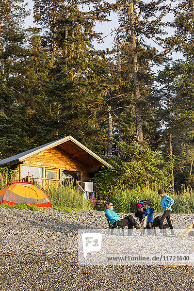 Two women and children on the beach with a National Forest Service public use cabin in the background  Hekseth Island  Southcentral Alaska  USA