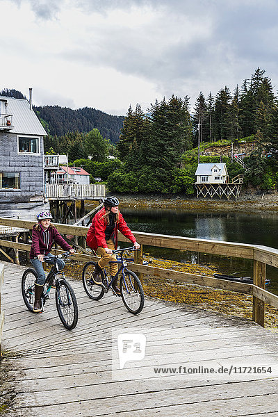 Mother and daughter bicycling on the historic oceanside boardwalk  Seldovia  Southcentral Alaska  USA