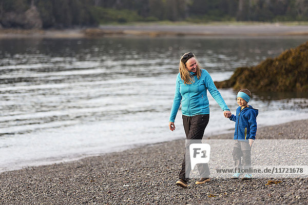 Mother and son walking along the beach  Homer  Southcentral Alaska  USA