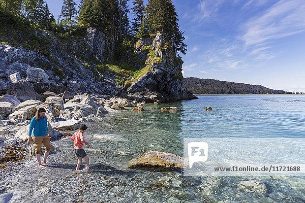 Mother and daughter on a rocky beach  Seldovia  Southcentral Alaska  USA