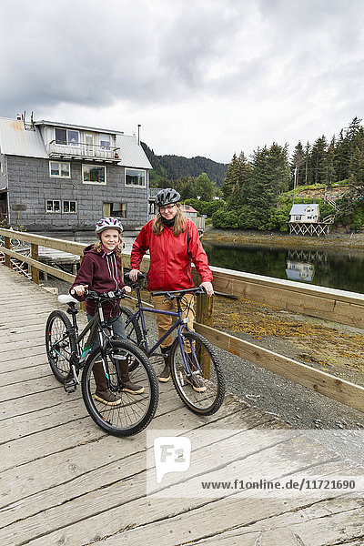 Mother and daughter with bicycles on the historic Seldovia oceanside boardwalk  Southcentral Alaska  USA