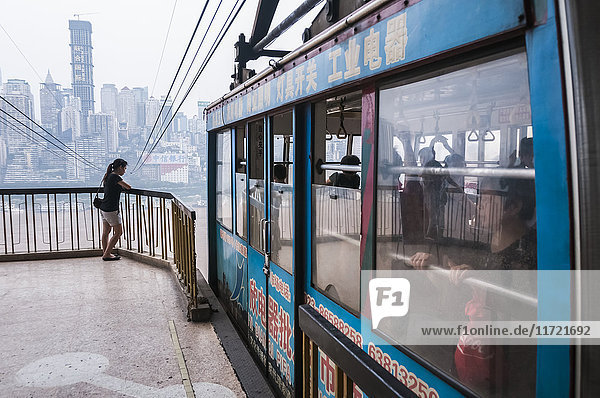 'Cable car crossing Yangtze river in Chongqing  the city as background covered by the fog; Chongqing  China'