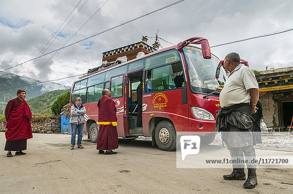 'Local bus from Daocheng to Sangrila  monks  tourists and local people traveling together  west of Sichuan province; Daocheng  Sichuan  China'