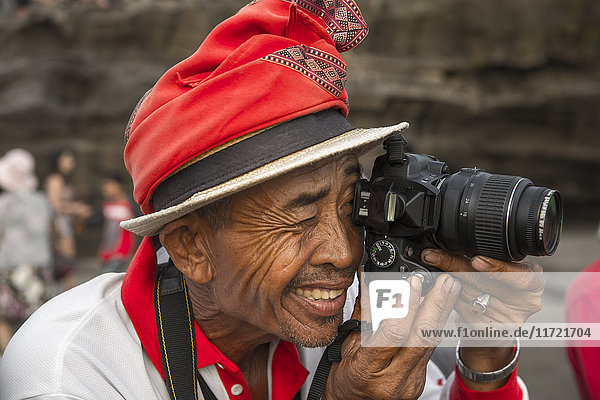 'Official photographer for tourists in Tanah Lot temple; Bali Island,  Indonesia'