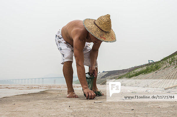 'A fisherman working with his net to get some small fish in Yangtze river; Chongqing  China'