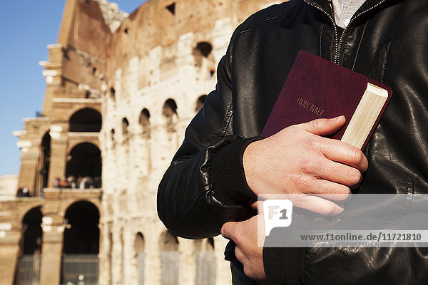 'A young man stands holding a Bible with the Colosseum in the background; Rome  Italy' 'A young man stands holding a Bible with the Colosseum in the background; Rome, Italy'