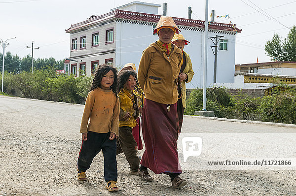 'A tibetan family walking on the street in Litang village; Litang  Sichuan province  China'