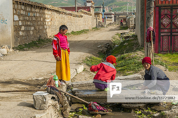 'Some tibetan kids washing clothes on the street in Litang village; Litang  Sichuan province  China'