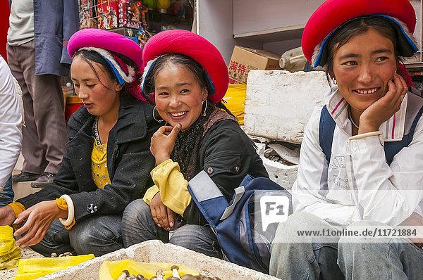 'Three young women sit at the market selling mushrooms; Shangrila  Yunnan province  China'
