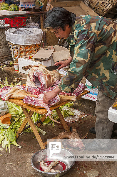 'A vendor prepares meat to sell in this market where we can see people from different minority groups and the daily life of Famous Shangrila village; Shangrila  Yunnan province  China'