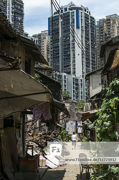 'Old neighborhood surrounded by skyscrapers  Chongqing is a city with really fast development that people cannot handle  having huge changes every year; Chongqing  China'