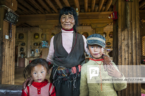 'Inside a traditional Tibetan house  big living room where an old woman and her grandsons pose for a photo; Daocheng  Sichuan province  China'