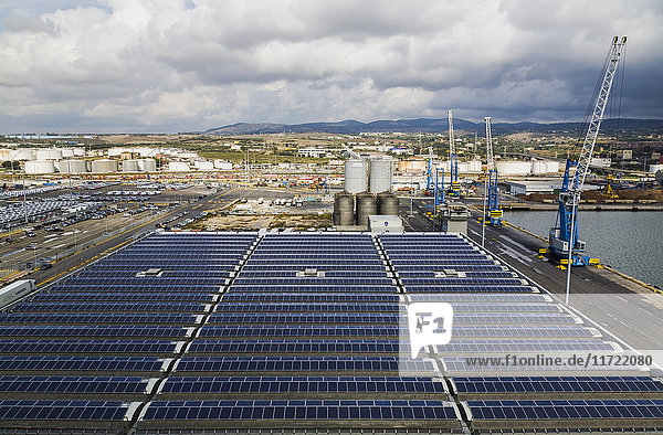 'Top view of warehouse building with solar energy collector panels on rooftop  port of Civitavecchia; Civitavecchia  Lazio region  Rome province  Italy'