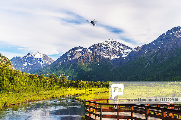 A man is standing on the Eagle River Nature Center boardwalk while a Black Hawk helicopter flies over head in the Chugach State Park in Southcentral Alaska  USA