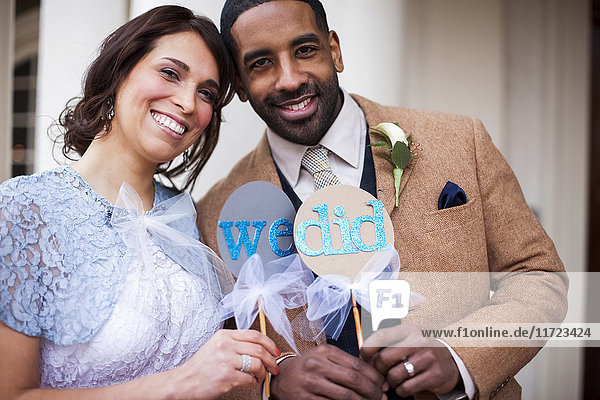 'A bride and groom pose with signs symbolizing their wedding vows; Portland  Oregon  United States of America'