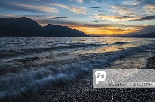 'Surf along the shore of Kluane Lake at sunset; Yukon  Canada'