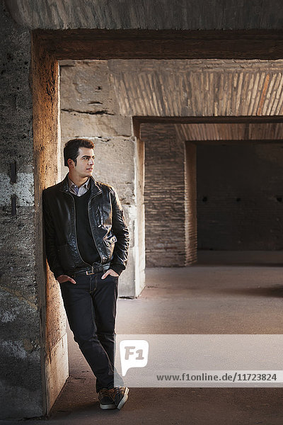 'Portrait of a young man standing against a wall with concrete facade; Rome  Italy'
