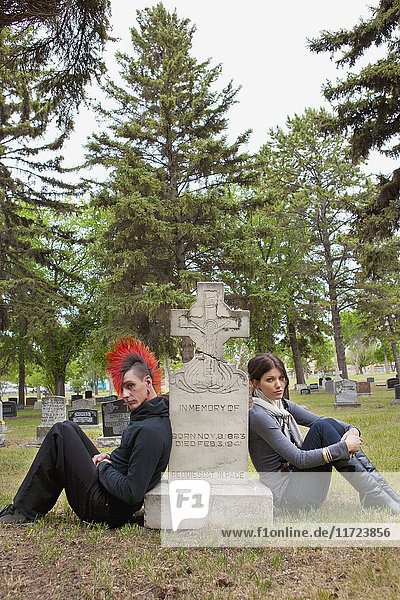 'A Young Man And Young Woman Sitting By A Tombstone; Edmonton  Alberta  Canada'