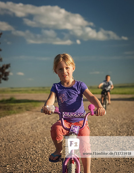 'A young girl riding her bicycle down a gravel road with her brother riding behind; Herschel  Saskatchewan  Canada'