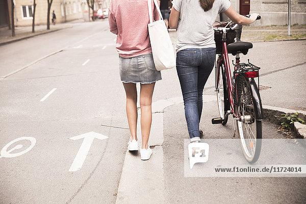 Young women walking with bike