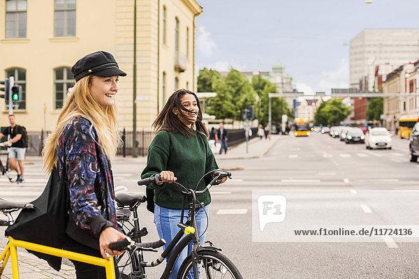 Two young women pushing bikes in town Two young women pushing bikes in town