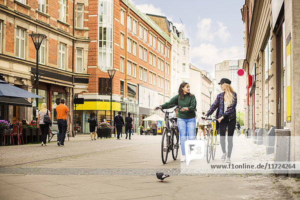 Two young women walking and pushing bicycles in old town