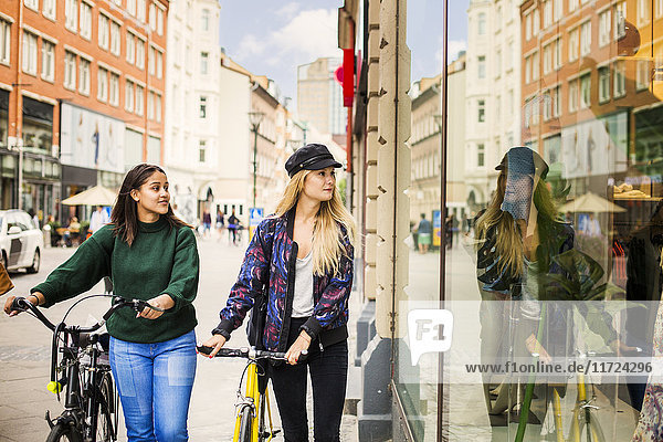 Two young women with bicycles looking at store window Two young women with bicycles looking at store window