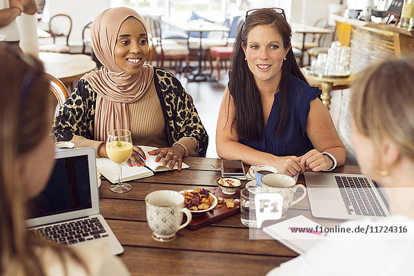 Businesswomen working during lunch in restaurant