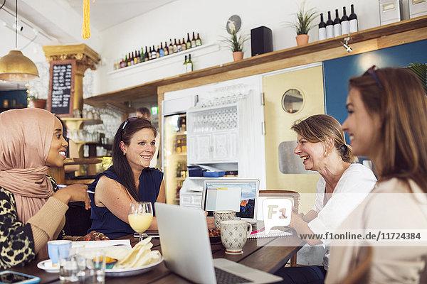 Businesswomen working during lunch in restaurant