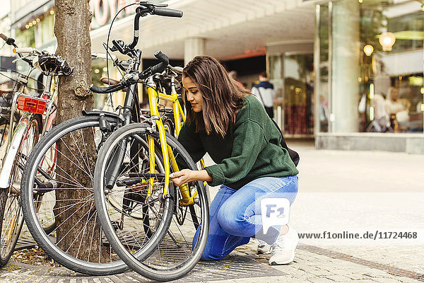 Young woman locking bicycle in town