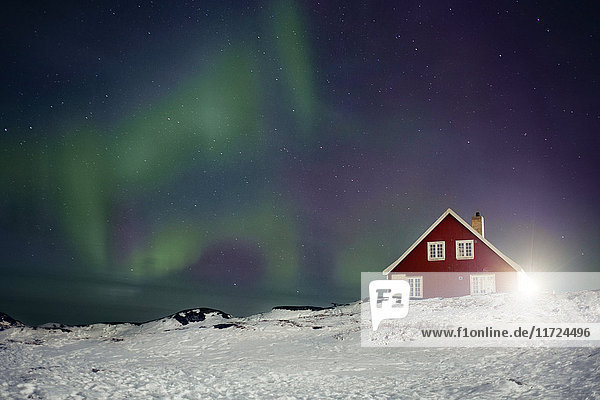 Northern light above red house